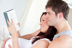 Pregnant woman and her husband reading a book Stock Photo