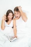 Pregnant woman and her husband reading book Royalty Free Stock Image