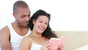 Pregnant woman and her husband reading a book. On the sofa stock video footage