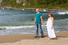 Pregnant woman and her husband by the sea. Stock Photography