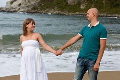 Pregnant woman and her husband by the sea. Royalty Free Stock Photo