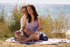 Pregnant woman and her husband sitting on the beac Royalty Free Stock Photography