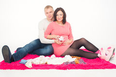 Pregnant woman and her husband with small baby shoes Royalty Free Stock Images