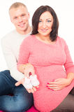 Pregnant woman and her husband with small baby shoes Royalty Free Stock Photos