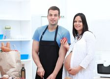 Pregnant woman and her husband standing together in the kitchen royalty free stock photos