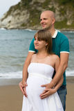 Pregnant woman and her husband strolling by the sea. Stock Photos