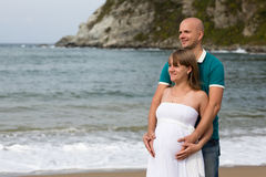 Pregnant woman and her husband strolling by the sea. Stock Photography