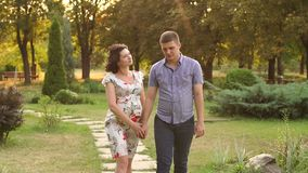 Pregnant woman and her husband are walking in park stock video footage