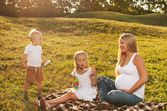 Pregnant woman with her kids. Beautiful blond pregnant women enjoying her older kids company. Mother with kids outdoors in sunlight. Mother's day concept Stock Photography