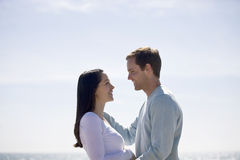 A pregnant woman and her partner embracing on the beach Royalty Free Stock Images