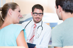 Pregnant woman and her partner seeing physician Stock Photos