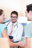 Pregnant woman and her partner seeing physician royalty free stock photos