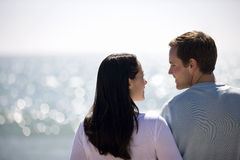 A pregnant woman and her partner standing on the beach, rear view Stock Images
