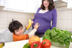 Pregnant woman with her son in kitchen Royalty Free Stock Images