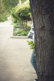 Pregnant woman in hiding behind the tree in park. Stock Photo