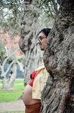 Pregnant woman hiding her face from behind a tree and boyfriend taking off her face, funny photo of pregnant stock images