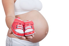 Pregnant woman hold in hand red baby boots Royalty Free Stock Photos