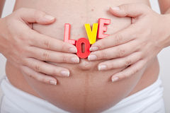 Pregnant woman hold in hand word girl Stock Photo