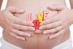 Pregnant woman hold word love on a belly Stock Photos