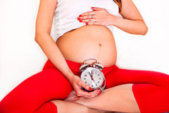 Pregnant woman holding alarm clock on her belly Stock Photo