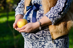 Pregnant woman holding an apple. Pregnant woman in blue dress holds a round yellow apple Stock Photography