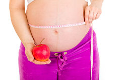 Pregnant woman holding apple. Close-up. Stock Photo