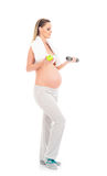A pregnant woman holding an apple and a dumbbell Royalty Free Stock Photo