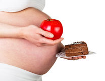 Pregnant woman holding an apple and  piece  cake  on white. Royalty Free Stock Images