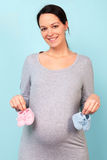 Pregnant woman holding baby booties Stock Images