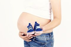 Pregnant woman holding baby booties. Nice studio photography, white background, blue jeans and pregnant belly Royalty Free Stock Photo