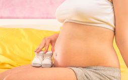 Pregnant woman holding baby booties shoes Stock Image