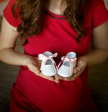 Pregnant woman holding baby boots. Pregnant woman holding little baby boots royalty free stock photography