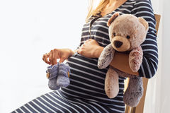 Pregnant woman holding baby boots and teddy bear. In her hands Stock Photos
