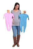 Pregnant woman holding baby clothes. stock photography