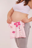 Pregnant woman holding baby clothes Royalty Free Stock Images