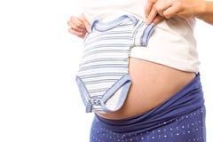 Pregnant woman holding baby clothes Stock Photos
