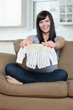 Pregnant Woman Holding Baby Clothing On Sofa Royalty Free Stock Images