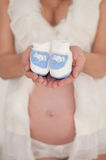 Pregnant woman holding baby shoes Stock Images