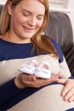Pregnant Woman Holding Baby Shoes Royalty Free Stock Images