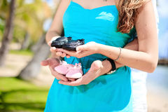 Pregnant woman holding baby shoes. Couple holding baby shoes. Couple are expecting twins: boy and girl Royalty Free Stock Photo