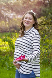Pregnant woman holding baby shoes in her hands in a park Royalty Free Stock Photo