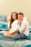 Pregnant woman holding baby shoes and husband Stock Photos