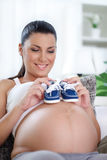 Pregnant woman holding baby shoes Stock Photography
