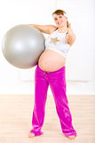 Pregnant woman holding ball and showing thumbs up Royalty Free Stock Photo