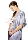 Pregnant woman holding belly and flower. Isolated on white Royalty Free Stock Images