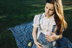 Pregnant woman holding belly sitting in sunlight royalty free stock image