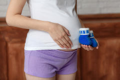 Pregnant woman holding blue baby booties on belly, closeup Stock Image
