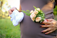 Pregnant woman holding bouquet of rose and booties Stock Image
