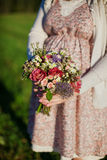 Pregnant woman holding a bouquet. Pregnant woman in a vintage dress holding a bouquet royalty free stock photo