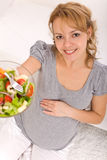 Pregnant woman holding a bowl of salad Stock Photos